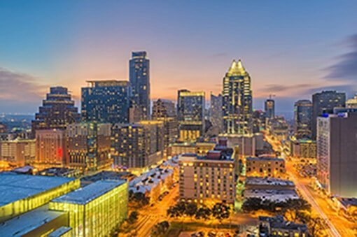 The city of Austin at dusk, lit up in front of a sunset sky, near where Austin Landmark Property Services provides Austin property management.